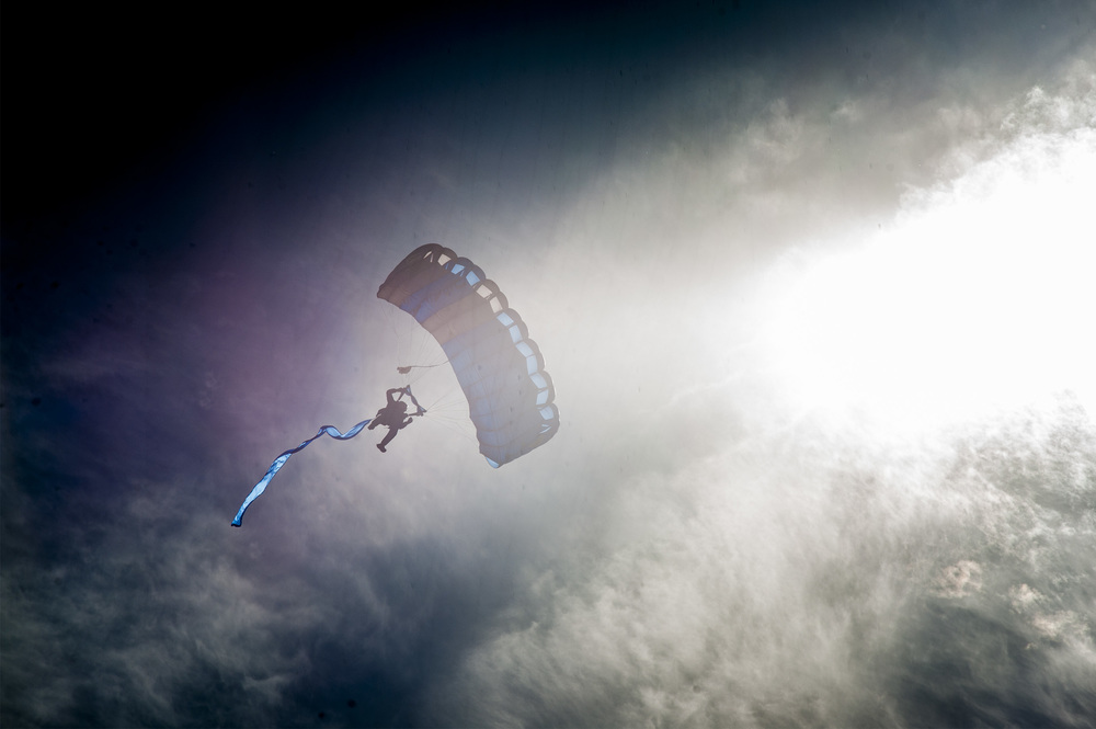 A student paratrooper of the U.S. Air Force Academy glides down to the earth during the annual Air Force Academy graduation parade on May 26, 2015. Families and friends from all over the country come to watch their sons and daughters walk in the parade as well as on graduation day.