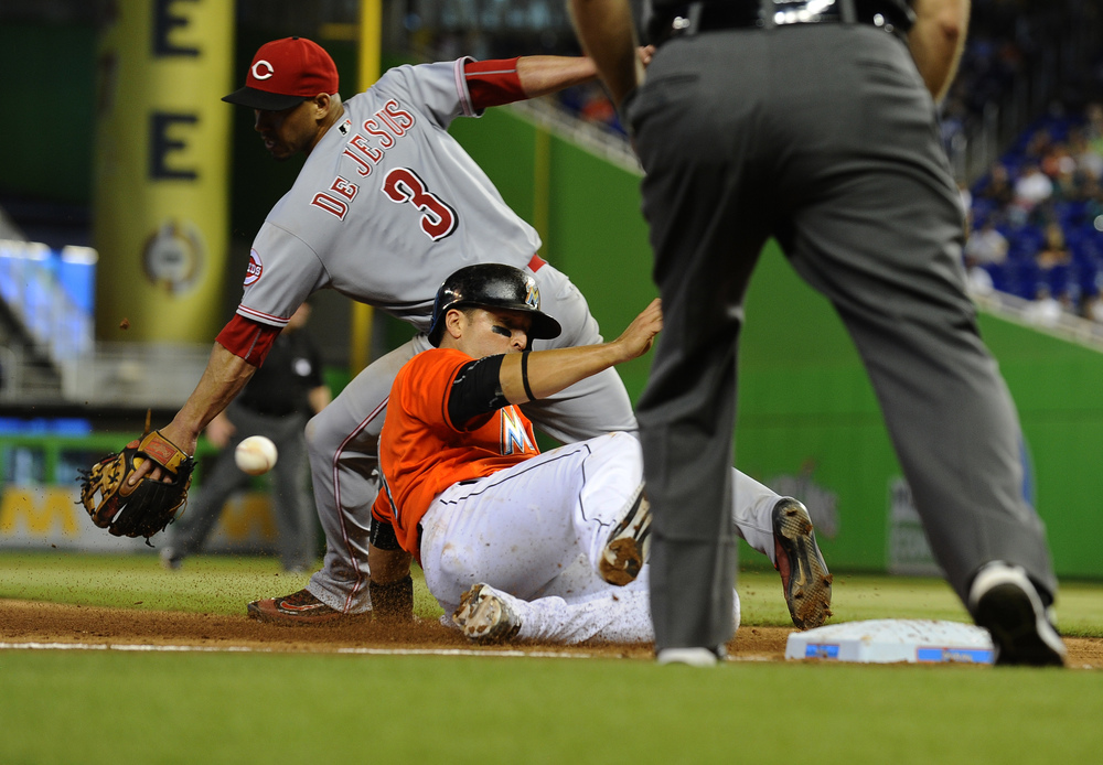 Miami Marlins catcher J.T. Realmuto (11) slides safely into third base as the ball gets away from Cincinnati Reds shortstop Ivan De Jesus (3) in the 6th inning of their game held at Marlins Stadium on July 10, 2016.