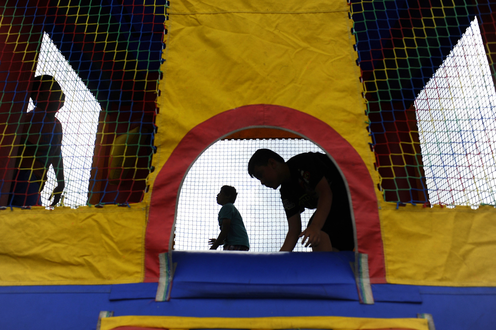 (From left) Ronald Salgado, 9, Jonathan Salgado, 10, and Axel Hernandez, 9, play in a bounce house during a community event held in Homestead celebrating the 25th anniversary of the Centro De La Salle community center that has assisted and protected many young undocumented children and families.