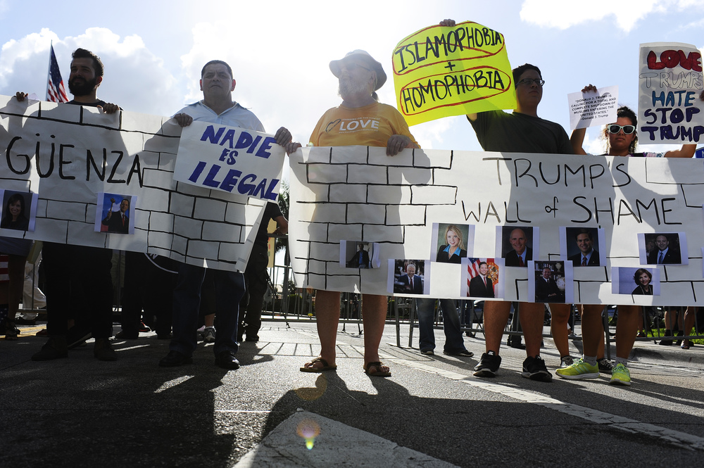 "Protesters stand across the street from the entrance to Trump National Doral Golf Resort on the corner of NW 87th Ave. and NW 41st St. in Miami, Florida, and unveil the ""Trump's Wall of Shame"" sign in protest. Republican Presidential nominee Donald Trump is holding a $50,000 a plate fundraiser with Governor Rick Scott and State Representative Carlos Trujillo."