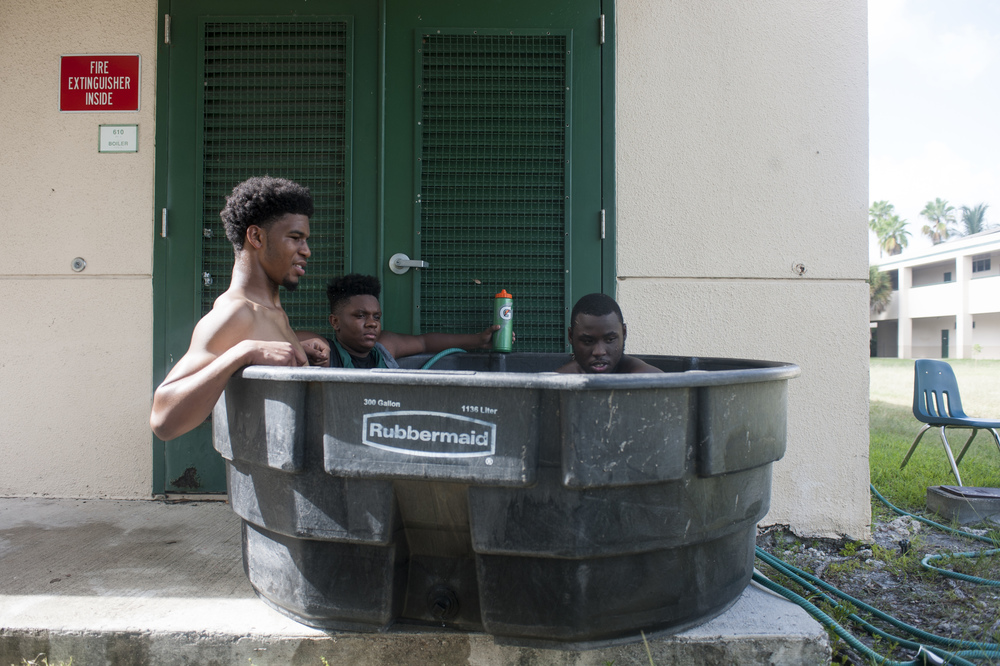Flanagan high school players sit in a cold tub during the first practice of the high school football season at Flanagan High School on Monday, Aug. 1, 2016. The reigning state champions look to repeat again despite the loss of key players from last year.