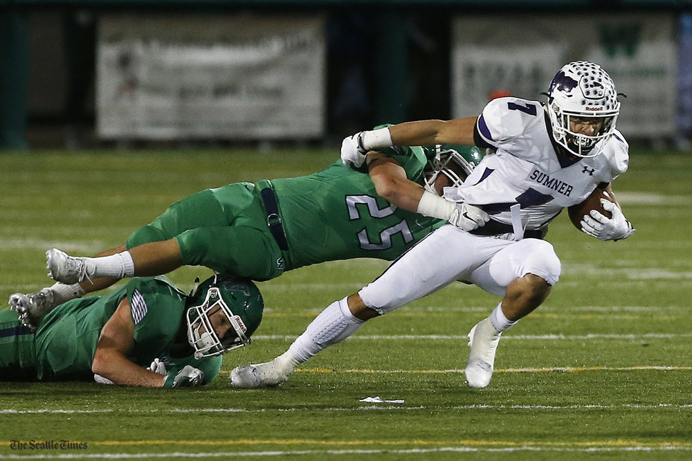 Sumner wide receiver Tre Weed gets held back by defenders while making a play during the 4A state quarterfinal game against Woodinville High School at Pop Keeney Stadium in Bothell on Friday, November 18, 2016.