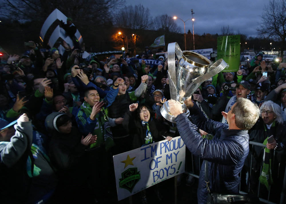 Seattle Sounders head coach Brian Schmetzer holds up the MLS Cup to the crowd outside of Boeing Field on Sunday, December 11, 2016, after being named MLS Cup Champions defeating Toronto FC in a penalty shootout.