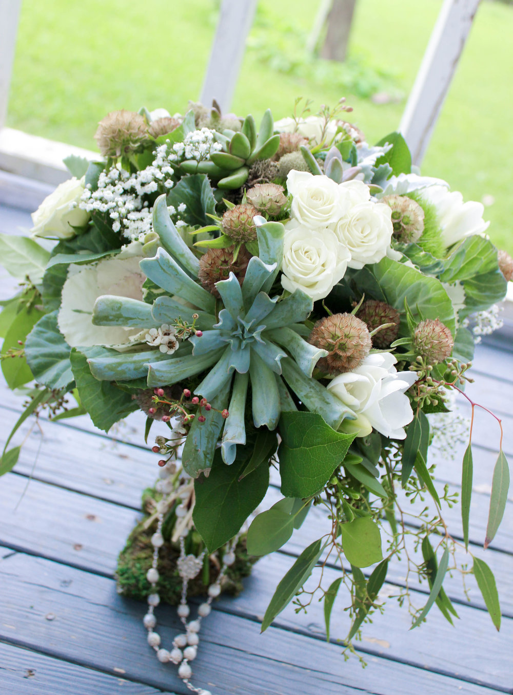 The bride's bouquet featured succulents, scabiosa pods, kale, eucalyptus, dusty miller and few ivory spray roses, freesia and baby's breath sprinkled in to add a touch of softness.