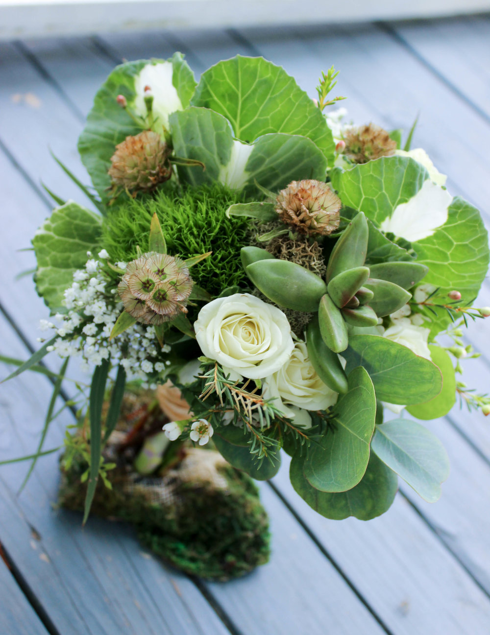 Tiny ivory spray roses are nestled in the kale and eucalyptus foliage for the junior bridesmaid.