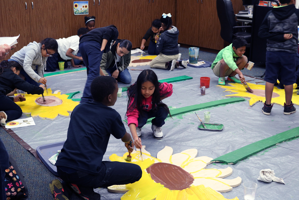 Hoover Youth Leadership group painting larger-than-life sunflowers to be installed in the school community garden.