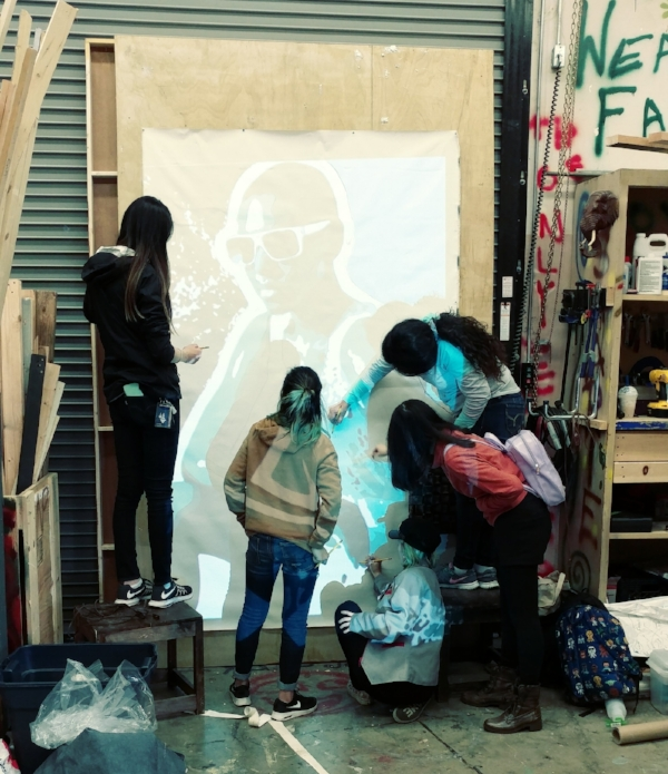 Students of the Oakland Tech Artesteem group along with the CCA student interns work on penciling in the image on canvas using a projector.