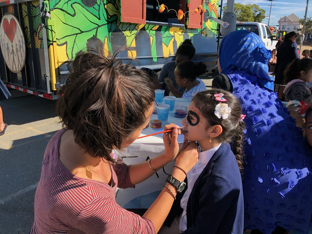 To the left our Hoover staff, Neeka, face painting a student with a sugar skull design.