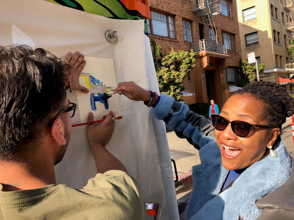 Local super heroine Councilwoman Lynette Gibson stencils an Oakland crane onto the canvas.