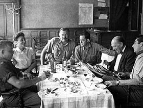 Ernest Hemingway at the head of the table.