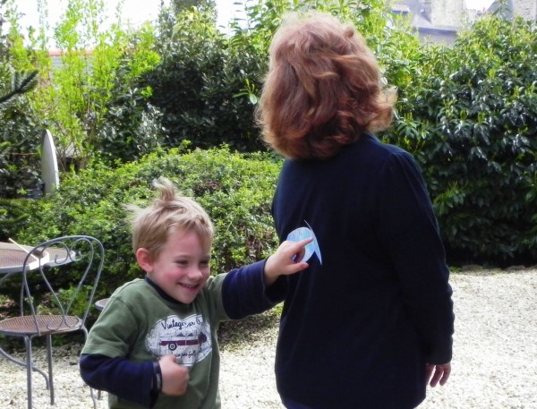 A French child taping a poisson d'avril to his mother's back.