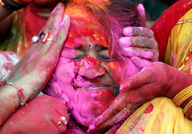 Woman getting smeared with color during the Indian Holi festival.