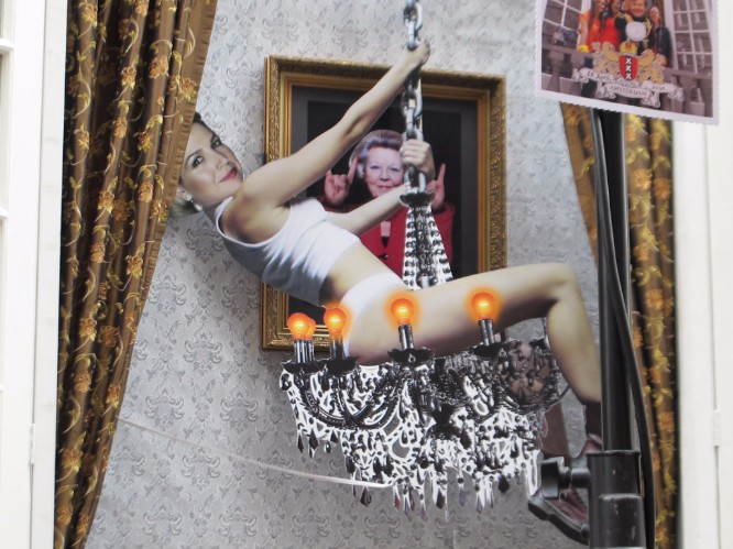 Satirical artwork – a cutout of a woman on a chandelier swinging past a photo of the former Queen.