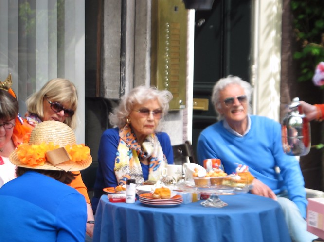 Sophisticated revelers having a sidewalk brunch outside their canal house.