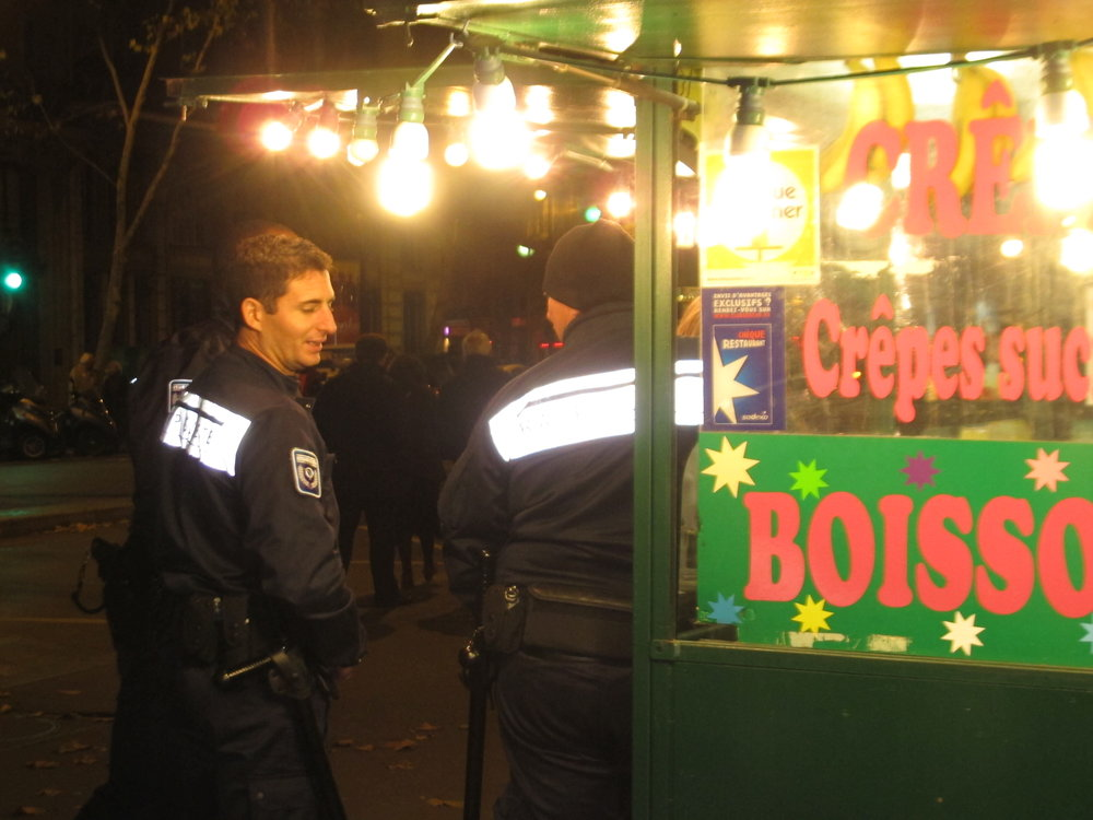 "Flics at a crêpe stand – the French version of cops at a donut shop. When this flic saw the flash from my camera, he turned around and said, ""No photos!"" Then he cracked up and said, ""Just kidding."" Photo: Elizabeth Kemble"