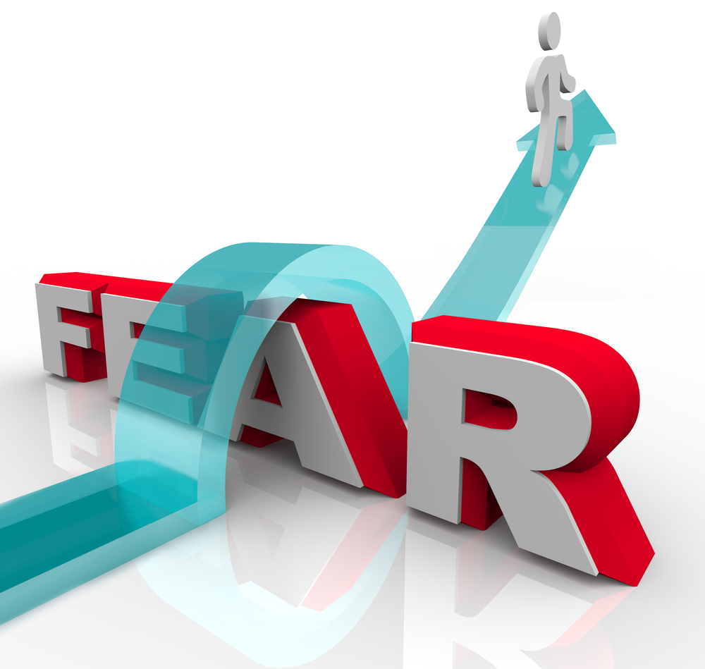 bigstock-A-man-jumps-over-the-word-fear-21701165.jpg