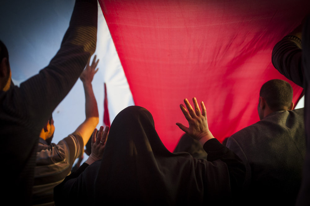 A woman walks under an Egyptian flag in Tahrir Square in Cairo Egypt. After the January 25th protest, demonstrators occupied Tahrir Square in Cairo, Egypt and demanded the overthrow of the regime of Egyptian President Hosni Mubarak.