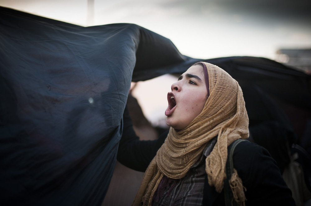 A girl holds the side of an Egyptian flag during a protest in Tahrir Square on February 8, 2011.