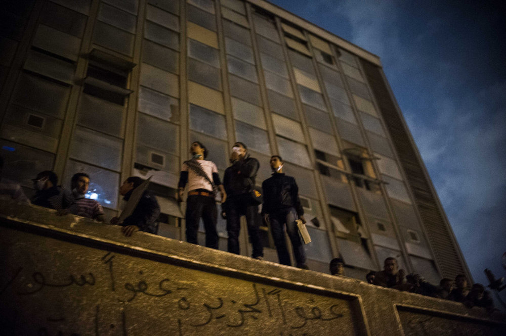 In November of 2011, Egypt is once again thrown into turmoil shortly before for the first democratic election. Men standing on the former American University in Cairo off Tahrir Square view the violent conflict between police forces and demonstrators on November 21st, 2011.