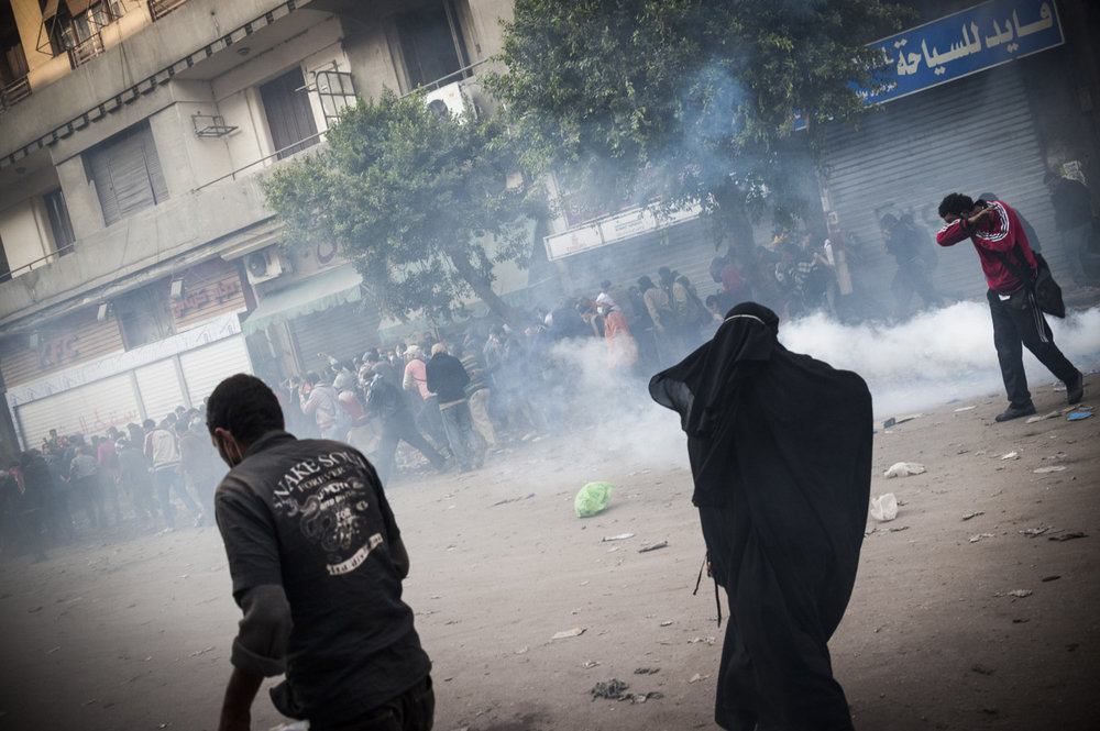A woman runs from teargas and rubber bullets shot off by the Egyptian riot Police on November 22nd 2011.  Protestors gather in Cairo's Tahrir square to speak out against SCAF, the Supreme Council of the Armed Forces, which has governed Egypt since the Revolution. The violent protests ended after a week with over 40 killed and thousands injured.