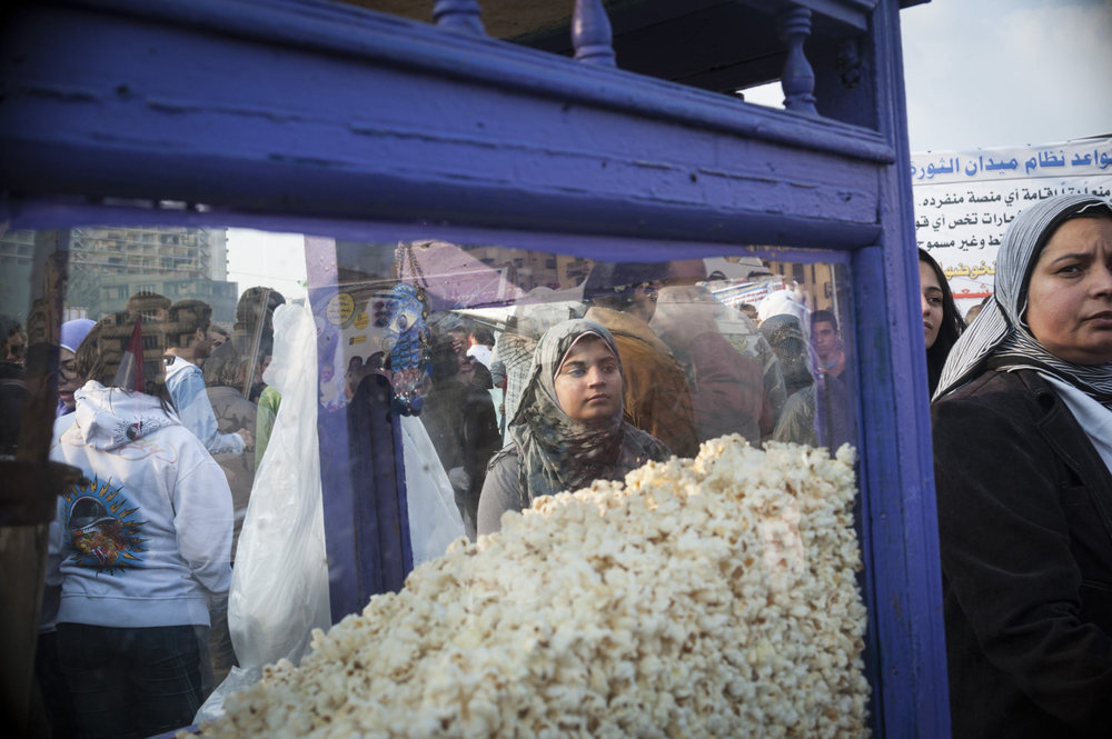 A girl stands near a popcorn vendor in Tahrir Square on November 25th, 2011.