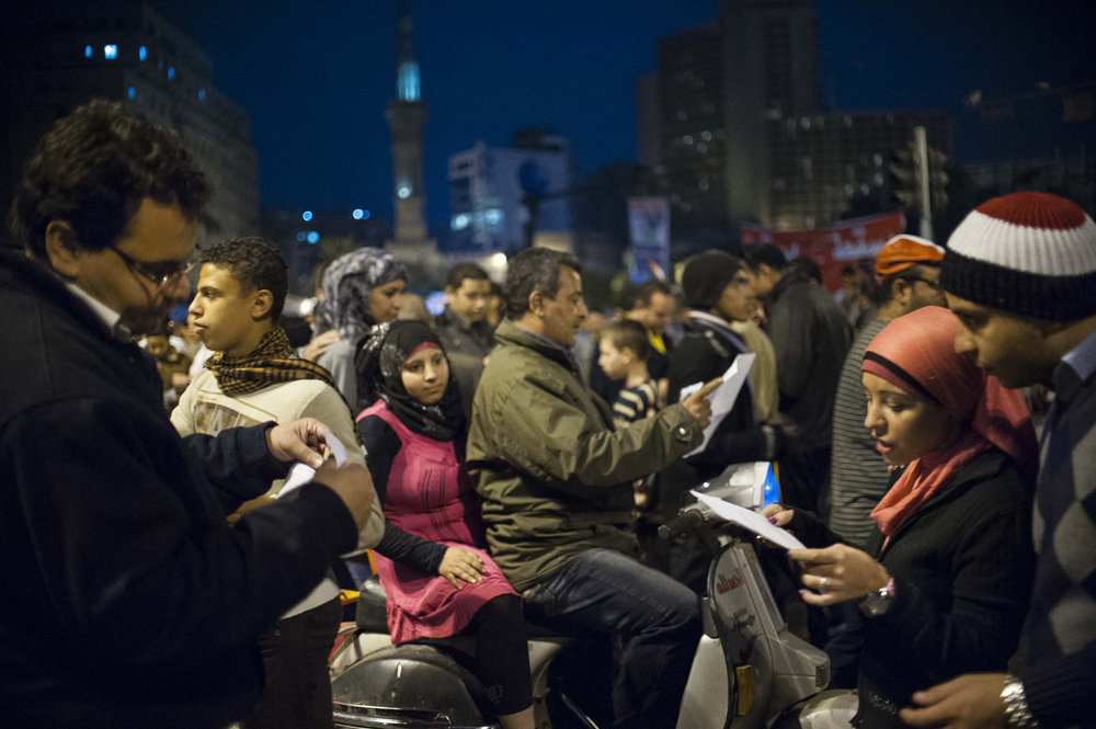 Egyptians read ballot forms with candidate information handed out in Cairo's Tahrir Square the night before elections on November 27th, 2011.