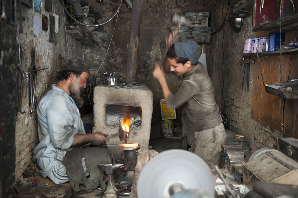 A father and son metalworking team work in downtown Kabul. The rate for skilled labor is 5 dollars a day and trades are traditionally handed down through the family.
