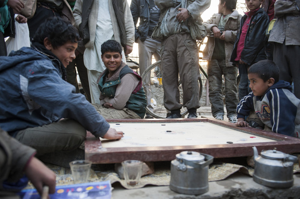 Children play Carambol in Cinema Park in Kabul. Mavid, age 12 right is playing Ravi, age 6. Though Ravi is the youngest and smallest player he has won his fifth straight game.