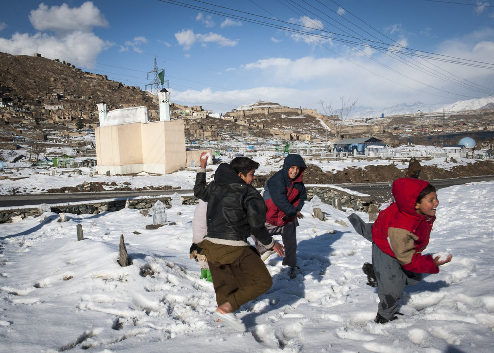 Kabul children, off for winter vacation play in the snow of the Shohadaie Saliheen Cemetery of Kabul, Afghanistan. Interestingly cemeteries are very social places in Afghanistan and are common for recreation.