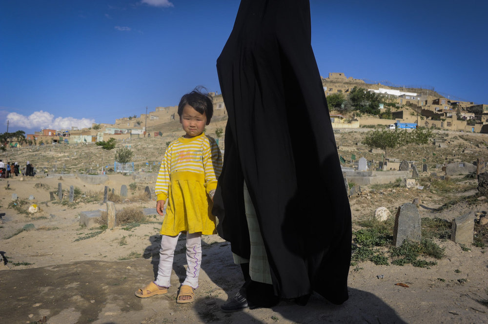 A Hazara girl and her mother visit a cemetery in Kabul, Afghanistan. Thursday evening's is the traditional time to visit cemeteries as it is the night before Friday- the traditional holy day for Muslims.