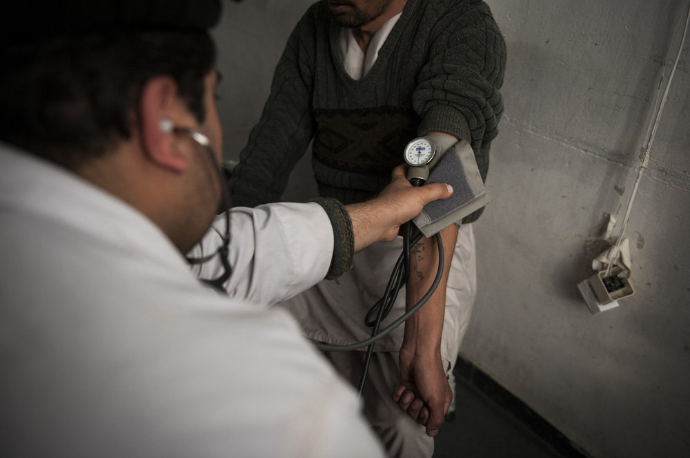 Dr. Zabullah, who has worked at the hospital for 10 years takes the blood pressure of a patient.
