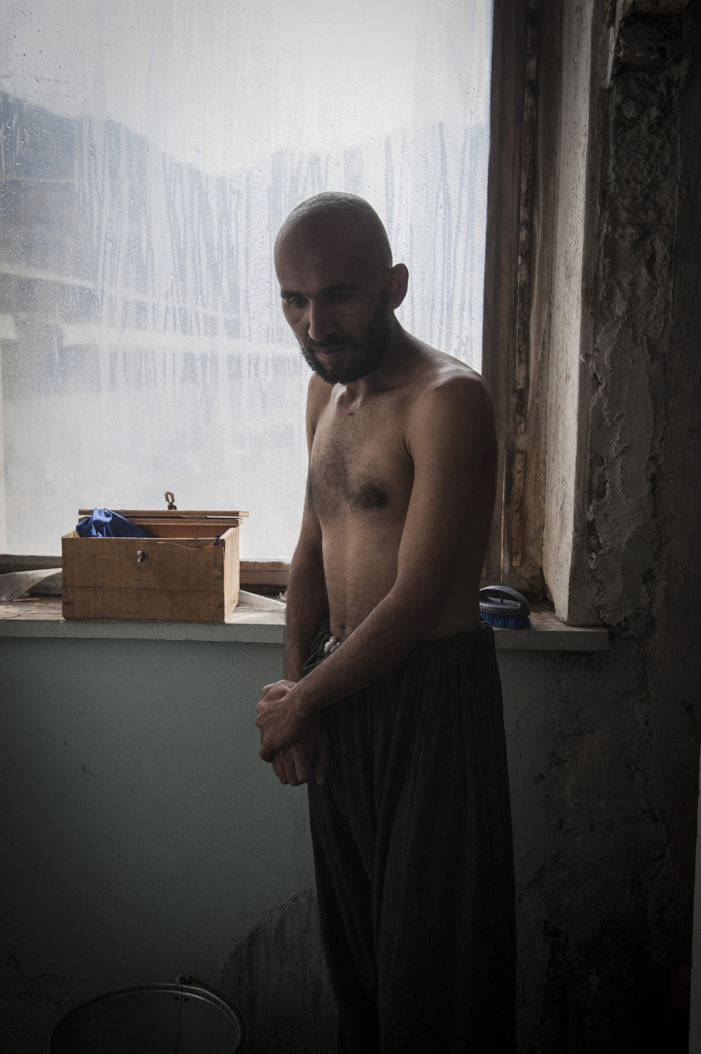 Abdullah Wahid enters the Jangaland rehabilitation clinic in Kabul, Afghanistan. The admittance procedure involves shaving the head as a sign of a new commitment.