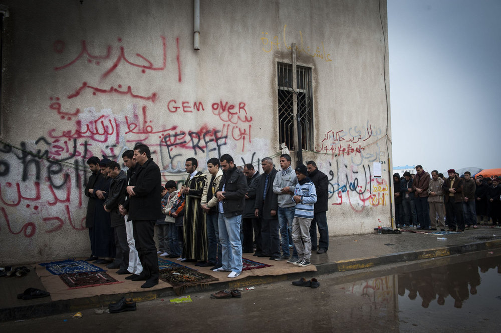 A group of men are sheltered from the rain during Friday Prayers in front of  Benghazi's downtown courthouse, men and women pray for safety and for the end of Gaddafi's reign. After a violent battle, the resistance members in Benghazi overtook city and set up an interim government based in the new capital of Benghazi.