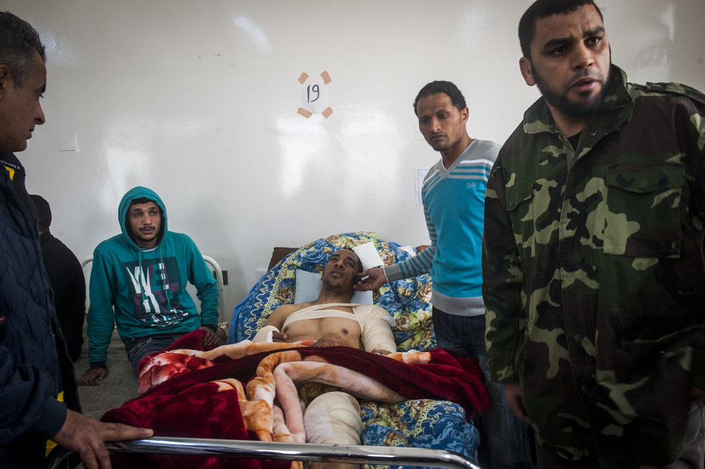 A man calls his family while friends attend to him in the hospital in Benghazi, Libya.