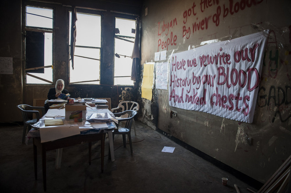 A woman reads a book in a room used to make signs and propaganda in the 17th of February Revolution Media Center.