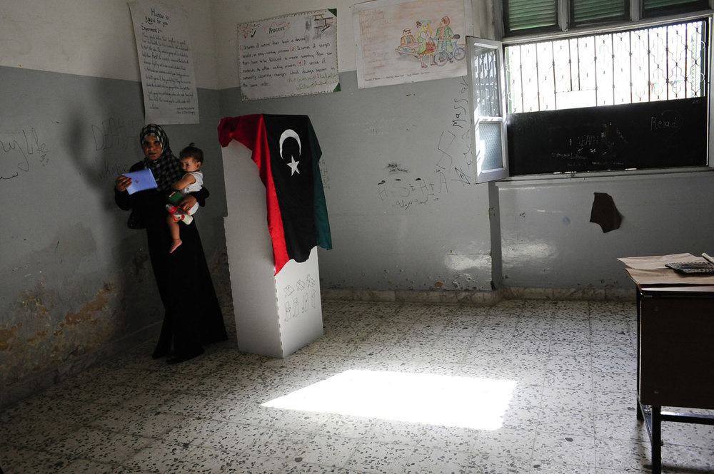 After voting a woman exits the poll with her child at Al Sakina School In Tripoli Libyans go to the polls for the first time in four decades on July 7th 2012. After 42 years of Muammar Gaddafi's reign, Libyans are participating in the first democratic election since 1969.