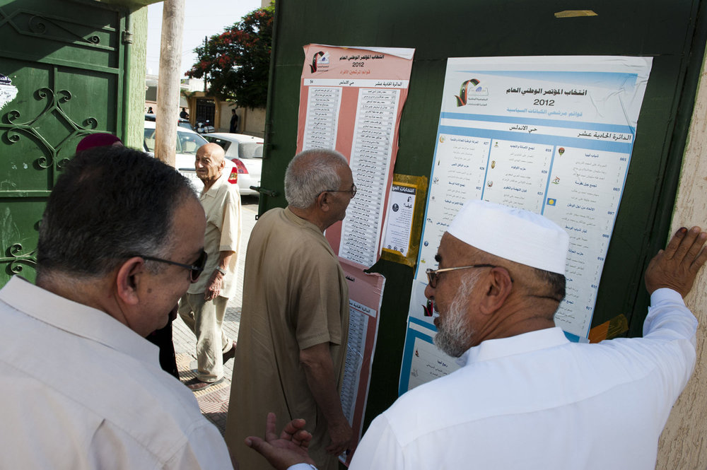 Men debate which polling station to go to. After 42 years of Muammar Gaddafi's reign, Libyans are participating in the first democratic election since 1969. Calls for boycott and election violence threatens the momentous day as campaigning drew to a close the day before the July 7th election.
