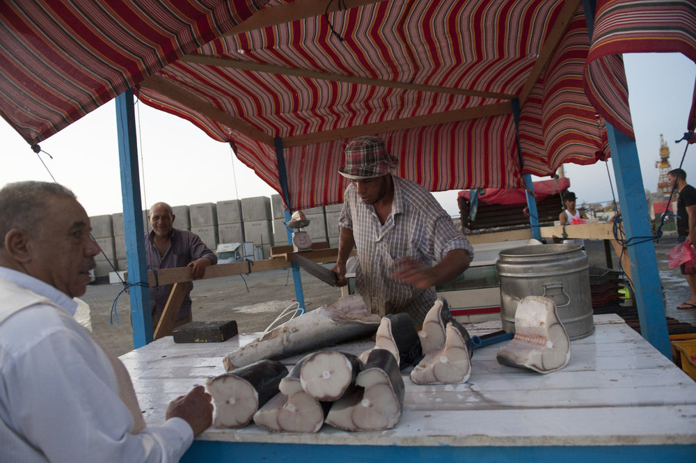 Al Araby, an Egyptian man cuts and sells shark pieces to a customer at a roadside fish market in Tripoli, Libya. Many Egyptians come to Libya to find work in the strong oil economy.