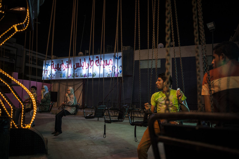 At Tripoli Land, an amusement park in Tripoli men wait for a ride to begin. While not required, men and women separate themselves on the ride as the nation is traditionally conservative.