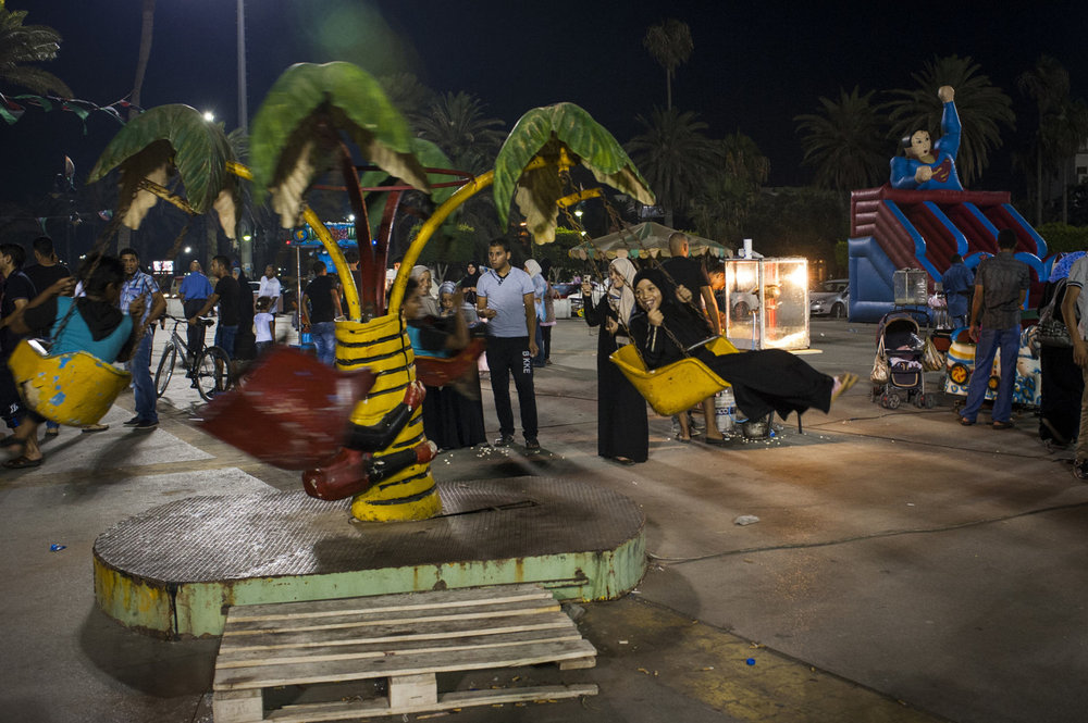 Children enjoy themselves on a ride in Martyr's Square in Tripoli, Libya. Public spaces morph into amusement parks during the summer months in Libya as the heat keeps many indoors all day.