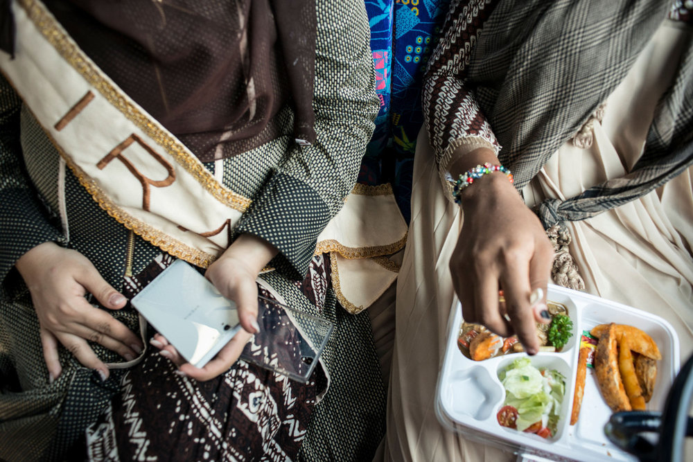 Miss Iran and Miss NIgeria eat lunch on the bus.