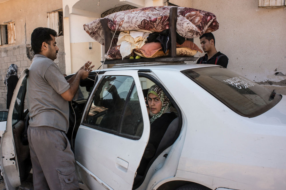 A family packs up to leave the Beit Hanoun area during a ceasefire in 2014.