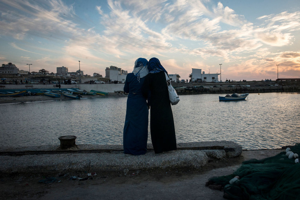 Girls watch the sun set at the harbor in Gaza City. While living in Gaza is undeniably tough, being a woman there is harder.