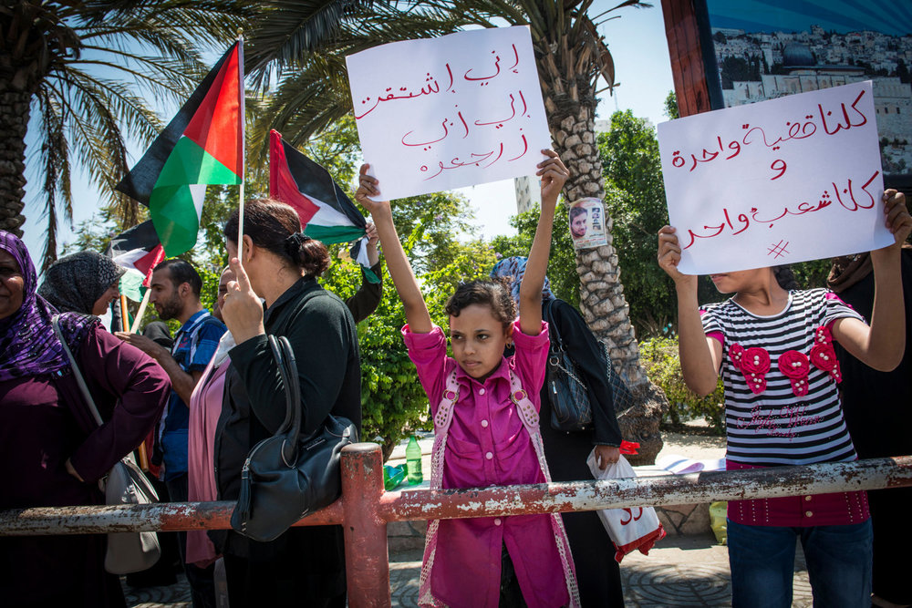 A young girl hold up a sign saying 'I really miss my dad. Bring him back home' at weekly protest for women against the partition of Gaza and the West Bank.