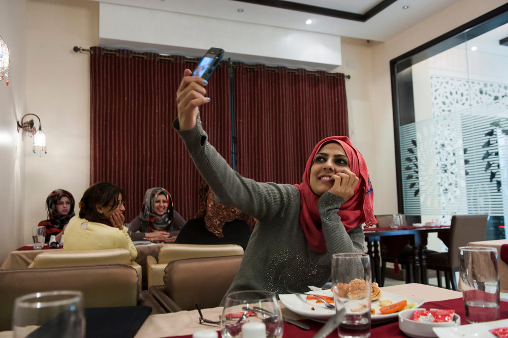 Doaa takes a picture of herself in a trendy cafe in Gaza City.