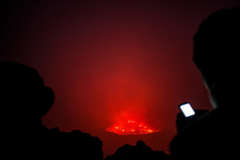 After dark, the lava lake is visable though the fog. Virunga is Africa's oldest national park and home to over 200 of the world's 800 remaining mountain gorillas. For two decades it has been at the centre of a war. Hundreds of rebels operate in the park and over 150 park rangers have died protecting it from them.