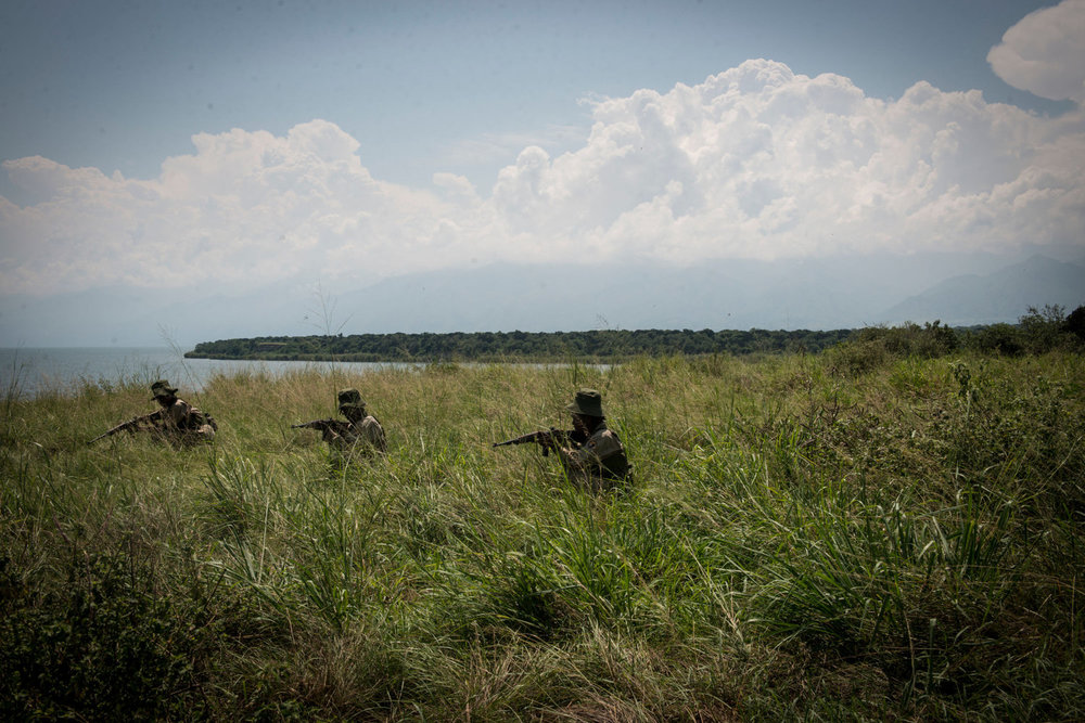 Rangers-in-Training rehearse military drills in the savannah. Virunga's park guards responsibilities eclipse those of a typical park guard as the area is known to have incidents with local rebel groups.