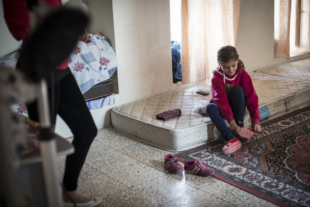 Besme changes her slippers in the bedroom for the family in the Cultural Center on October 30th, 2014 in Midyat, Turkey.