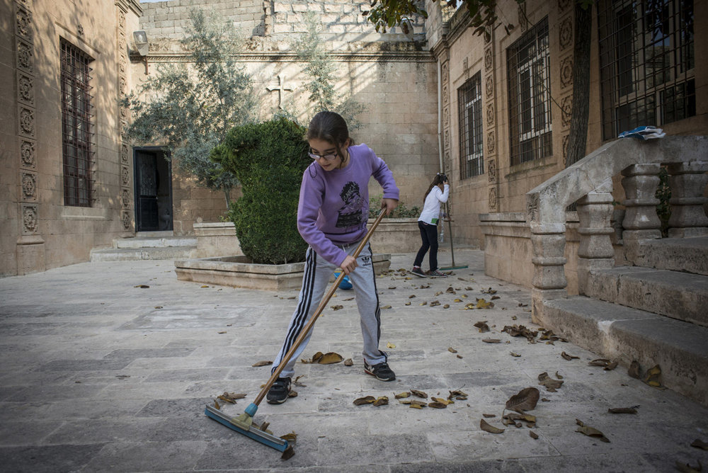 An Assyrian girl cleans up leaves in the courtyard of Mor Barsaumo before her Aramaic lesson on October 30th, 2014.