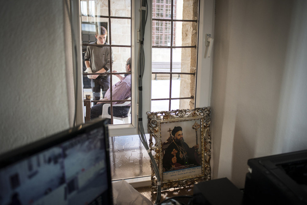 A portrait of a holy figure and CCTV cameras used to monitor the security of the church, where there has been attacks near a window looking out into the courtyard on October 30th, 2014 at Mor Barsaumo church in Midyat, Turkey.